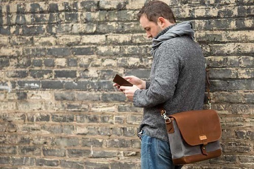 Man With Messenger Bag Typing On Cellphone